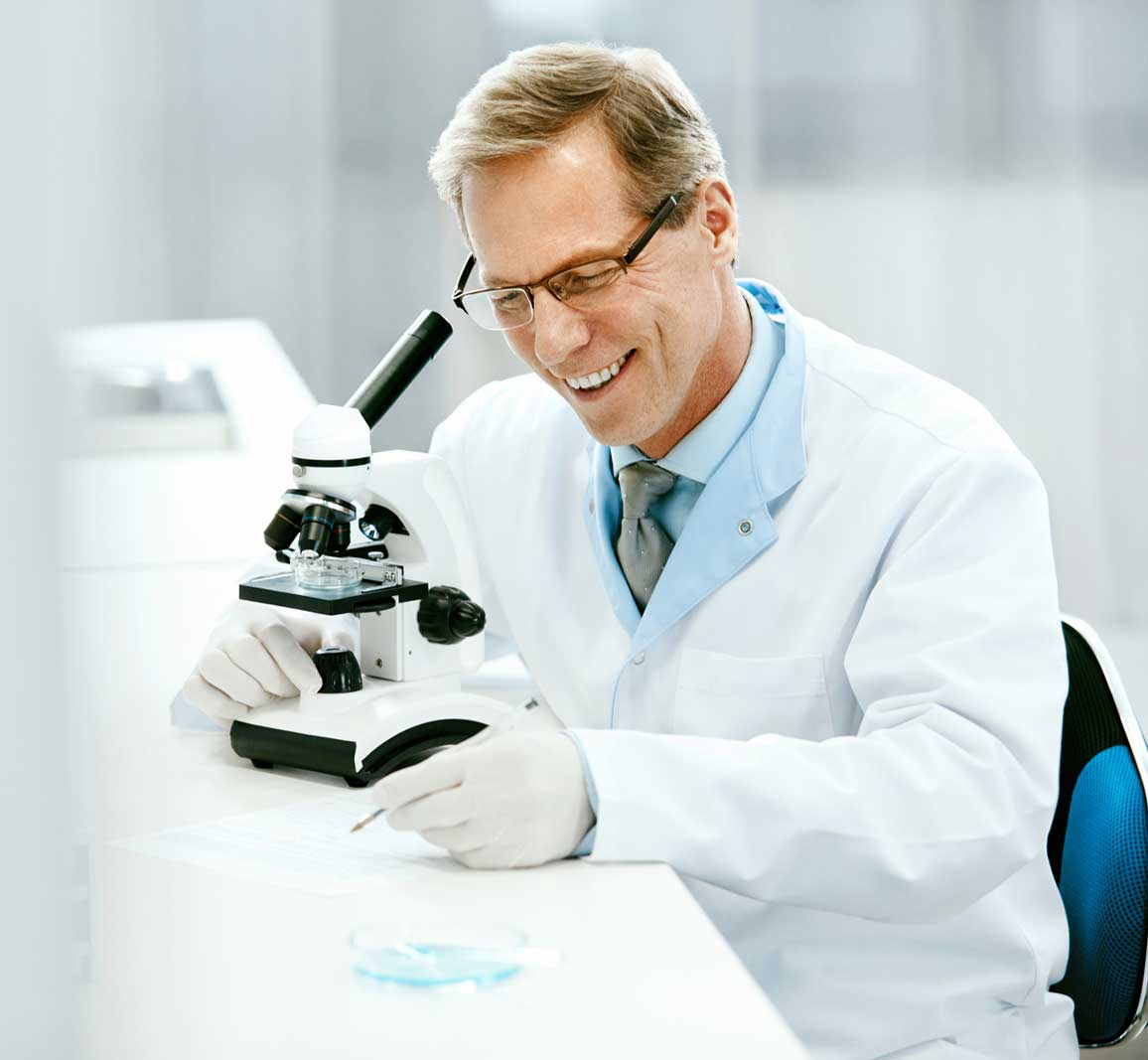 Clinical Test. Scientist With Microscope In Laboratory